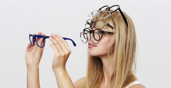 Woman choosing multiple pairs of glasses