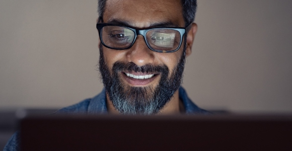 Man in front of computer wearing glasses